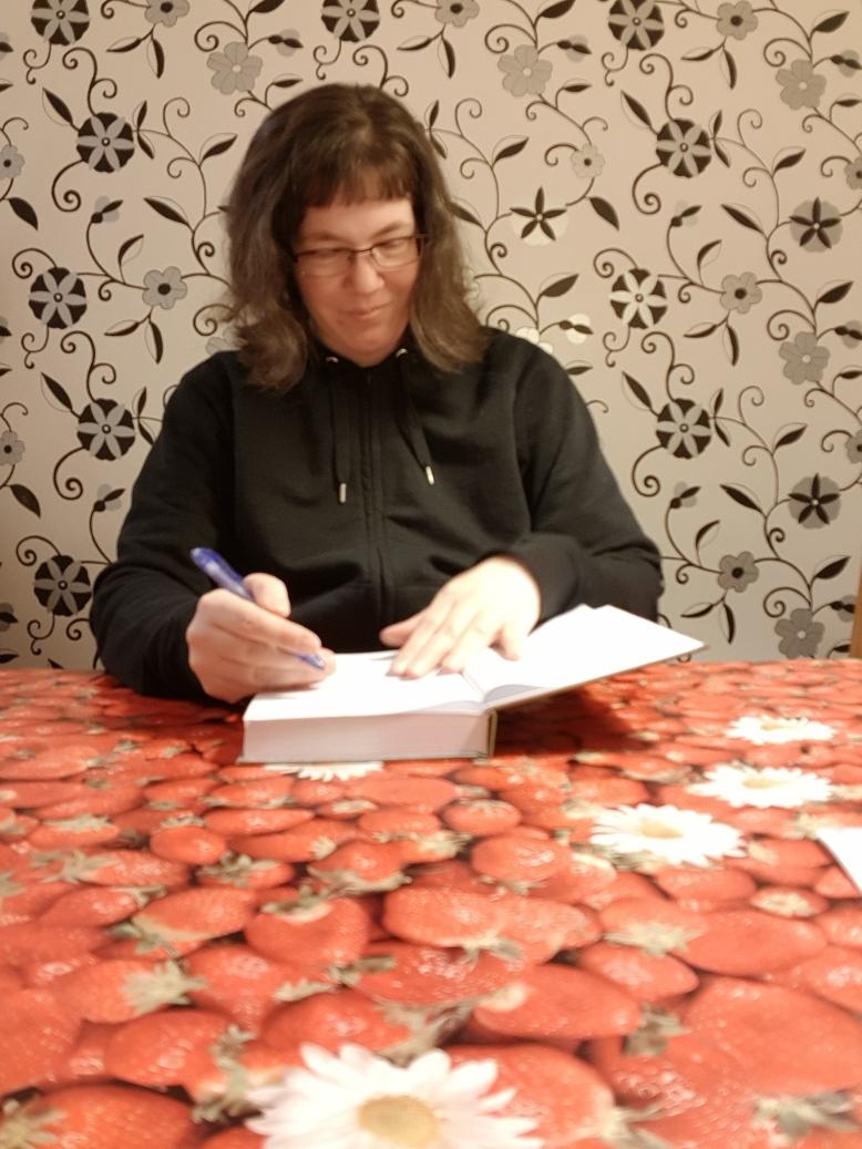 Lena Petersson signerar en bok. Foto: Lena Petersson.