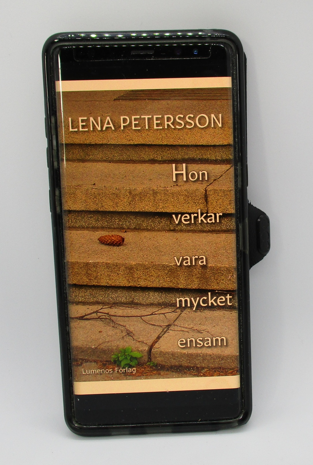 """E-boken """"Hon verkar vara mycket ensam"""" öppnad i en mobiltelefon. Foto: Lena Petersson."""
